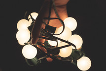 Hands holding a string of christmas lights.