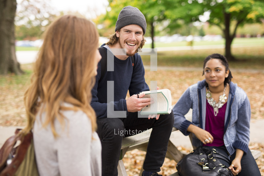 students having a Bible study at a picnic table