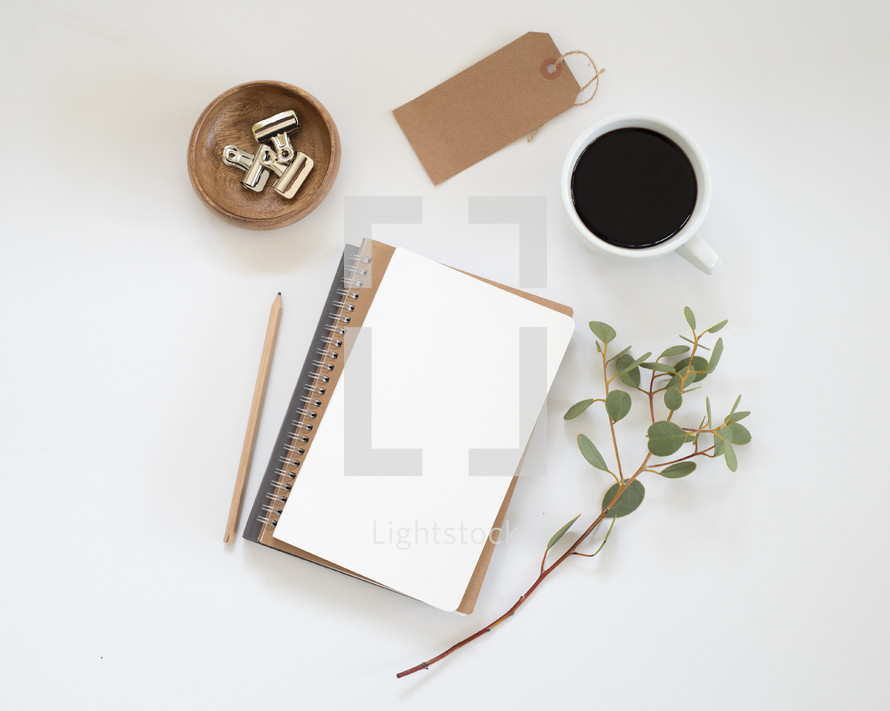 stack of journal, eucalyptus twig, pencil, clips in a bowl, gift tag, and coffee cup