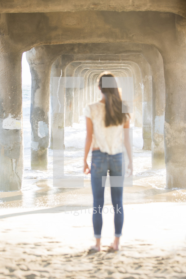 woman standing under a pier on a beach