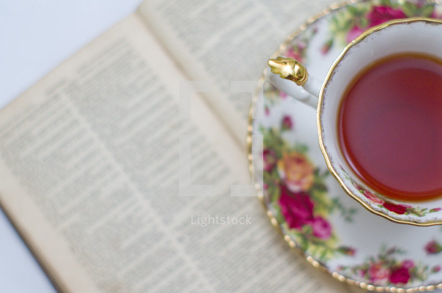 tea in a tea cup and an open book