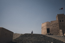 man walking up steps to a fortress