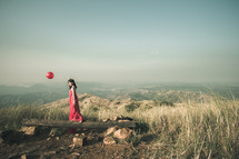 a woman on a mountaintop in a red dress holding a red balloon