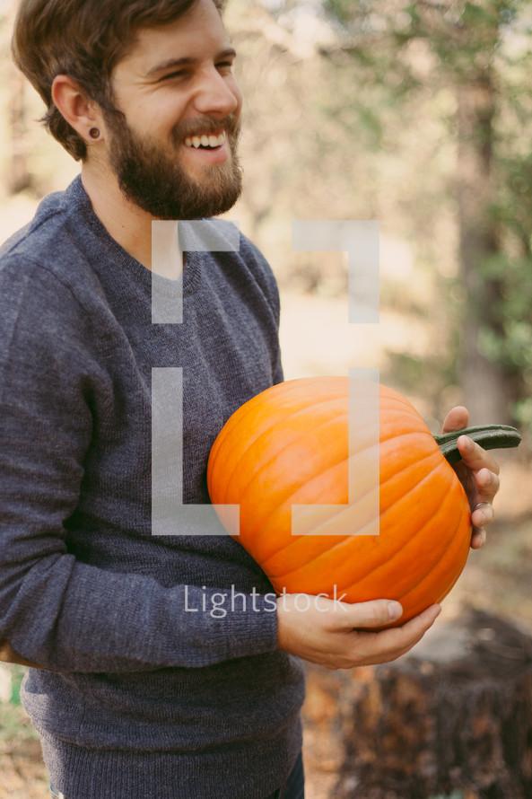 a man holding a an orange pumpkin