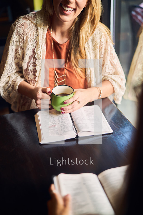 women reading a Bible and discussing scripture
