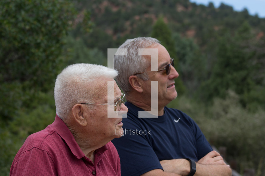 side profile of men standing together outdoors