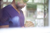 African-American man in prayer through a window