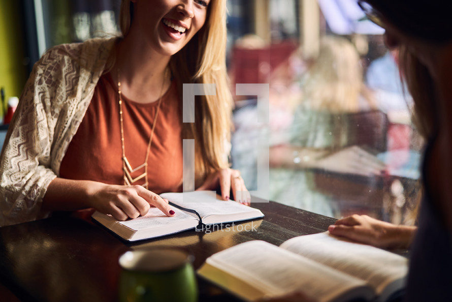 women reading Bibles and discussing scripture