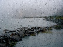 rain drops on a window with view of a shore