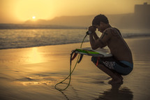 squatting surfer with his head bowed in prayer over his surfboard