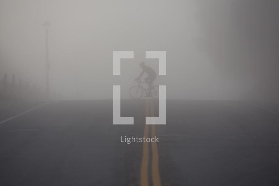 man riding a bicycle across a street under thick fog