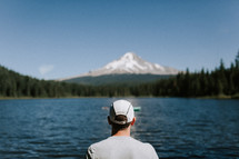 man looking out at a mountain lake