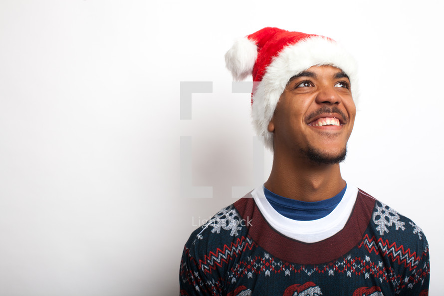 man in an ugly Christmas sweater and santa hat smiling looking up