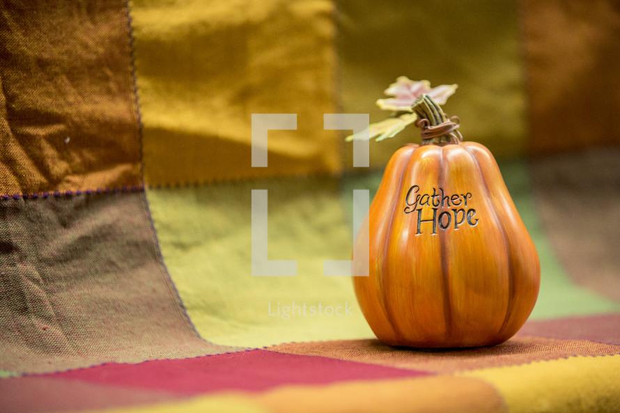 words GATHER HOPE on a pumpkin