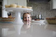 a little girl looking up at dessert on the counter in the kitchen