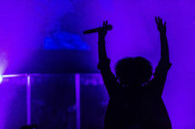 A woman on stage with her arms raised in worship.