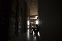 a woman sitting alone in a dark hallway