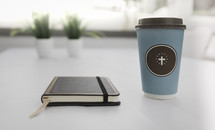 coffee cup with a cross and journal