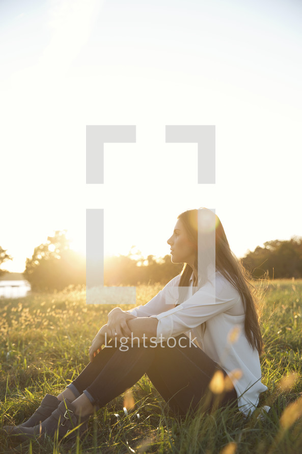 a woman sitting in the grass under sunlight