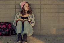 Teenage girl back to school studying, ready bible, campus, alone in a school hallway, wall, devotional
