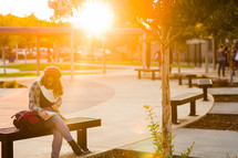 Teenage girl back to school studying, ready bible, campus, golden light, alone on a bench, devotional