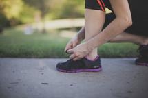 Runner tying shoes on a sidewalk.