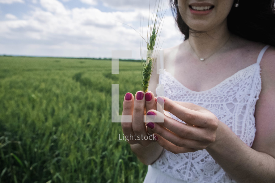 a woman holding green wheat