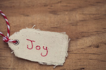 "A Christmas gift tags, reading ""Joy"", on a wood grain background."