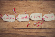 "Christmas gift tags, reading ""Joy,"" ""Hope,"" ""Love,"" and ""Peace,"" lined up on a wood grain background."