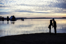 silhouette of a couple kissing in front of water