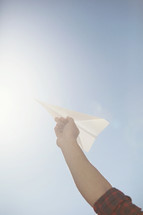 Raised hand holding a paper airplane.