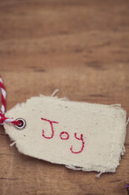 "A Christmas gift tag with ""Joy"" written on it, on a wood grain background."
