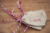 "A stack of Christmas gift tags, the top one reading ""Love,"" on a wooden table."
