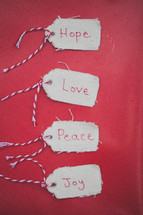 "Christmas gift tags reading ""Hope,"" ""Love,"" ""Peace,"" and ""Joy"" on a red background."