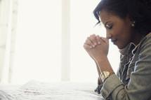 An African American woman kneeling in prayer beside her bed.