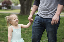 A little girl holding hands and laughing with her father.