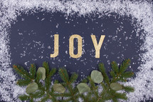word joy with snow border and pine