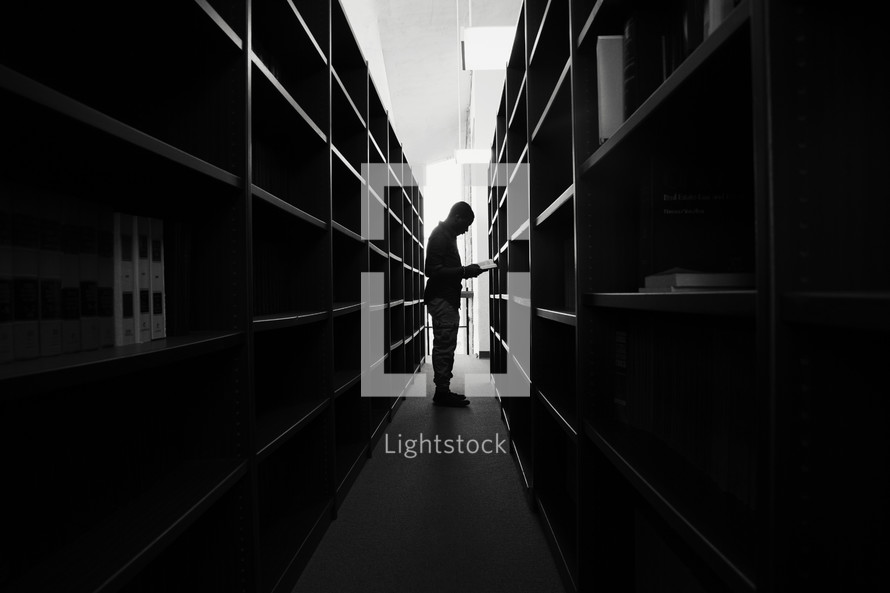 a man looking for books in a library