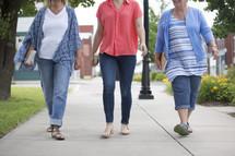 women walking on a sidewalk carrying Bibles