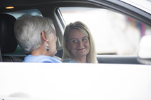 mother and daughter in a conversation while riding in a car