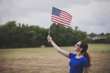 woman wearing stars and stripes sunglasses and a temporary tattoo - holding an American flag