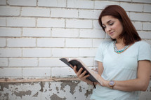 a young woman smiling as she reads a Bible in front of a white brick wall