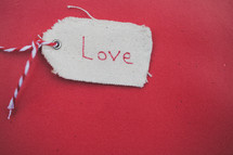 "A Christmas gift tag reading ""Love,"" on a red background."