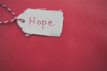 "A Christmas gift tag reading ""Hope,"" on a red background."