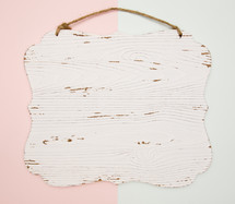 pink and blue background with white wood sign