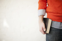 man holding a Bible at his side