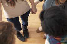 Women holding hands in a prayer circle.