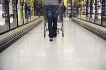 a man pushing a shopping cart through a grocery store
