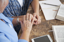 holding hands in prayer at a woman's group Bible study
