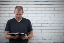 a man reading a Bible standing in front of a white wall